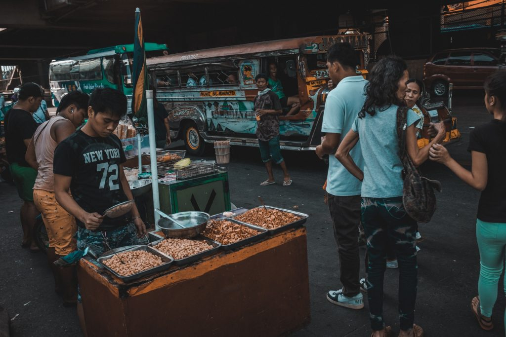 Philippine street with food vendors and jeepneys