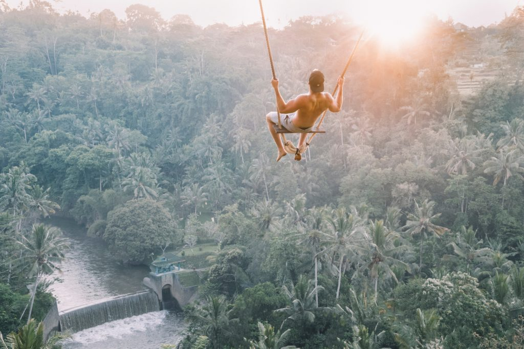 man on a swing above a jungle